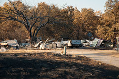 Destruction of a wildfire. Charred cars in the yard of a burned down house Stock Photography