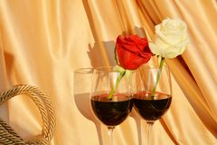 Destructive passion. Two different roses in two glasses of red wine, on an elegant background, pointing out the destructive passion Stock Image