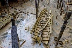 Destruição encalhada do barco de madeira pequeno com partes de madeira toda ao redor após a tempestade Fotos de Stock Royalty Free