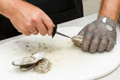 Desvainar ostras frescas con un cuchillo Fotos de archivo libres de regalías