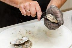 Desvainar ostras frescas con un cuchillo Foto de archivo libre de regalías