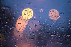 Deszcz krople na okno z drogą zaświecają bokeh obrazy stock