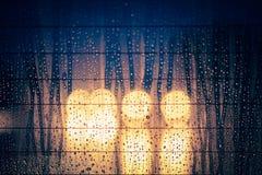Deszcz krople na okno z nocy drogą zaświecają bokeh fotografia stock