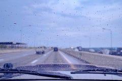 Deszcz opuszcza na car's windscreen, pada dzień wzdłuż autostrady obrazy royalty free