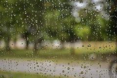 Deszcz opuszcza na samochodowym okno z światłem słonecznym, mokry szkło, deszczowy dzień zdjęcia royalty free