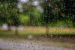 Deszcz opuszcza na samochodowym okno z światłem słonecznym, mokry szkło, deszczowy dzień zdjęcie stock