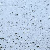 Deszcz opuszcza przy okno, kwadratowy i błękitnawy obraz royalty free