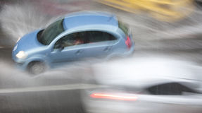 Deszczowy dzień w mieście: Napędowi samochody w ulicie uderzają h Obrazy Royalty Free