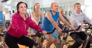 Det äldre folket gör sportar på motionscykeler arkivfoto