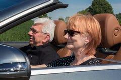 Det äldre paret kör med en lyxig konvertibel bil royaltyfria foton