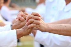 Det äldre tålmodiga folket sammanfogar handen tillsammans och stöttar sig för att uppmuntra god hälsaliv royaltyfria bilder