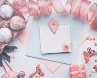 Det älskvärda påskhälsningkortet på pastellfärgad färg, förlöjligar upp med äggbandet, gåvaasken och garnering arkivfoton