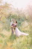 Det älskvärda vertikala fotoet av nygift personparen som rymmer sig på bakgrunden av det soliga fältet Royaltyfri Bild