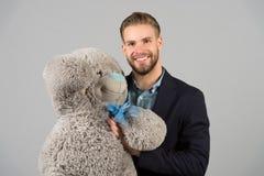 Det är aldrig för sent att ha lycklig vuxenliv Man den stora nallebjörnen för hols, grå bakgrund Begrepp för födelsedaggåva nalle arkivfoto