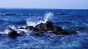 Det ?r ett h?rligt landskap var en v?g kraschar mot ett bl?tt hav vaggar av Udo, den Jeju ?n arkivfoto