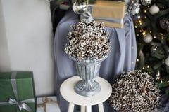 Det är många kottar i en grå vas på en vit stol mot bakgrunden av ett grönt gran-träd med en gul girland och gåvor royaltyfri foto