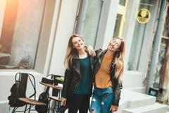 Det är roligt går med bästa vän! Två härliga kvinnor som går utomhus- krama och skrattar på höstgatan arkivbild