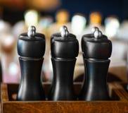 Det är salta shaker med salt, svart Betoningen är på dem De står i ett kafé och väntar på besökare att ta dem I baksidan royaltyfri foto
