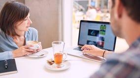 Det åtsittande skottet av kvinnan som ser bärbara datorn över, mans skuldran Royaltyfri Foto