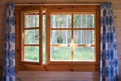 Det öppna fönstret med den naturliga träramen och blått blommar gardiner morgonskogsikt Soluppgång i landet Royaltyfri Fotografi