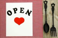 Det öppna tecknet med den röda rutiga bordduken och gjutjärn skedar och dela sig Arkivfoto