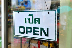 Det öppna tecknet som var brett till och med exponeringsglaset av fönstret i regnig dag med det hållande paraplyet för mannen, re Royaltyfri Foto