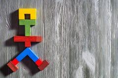 Det abstrakta diagramet av en gå man av färgrika träpussel Arkivbilder
