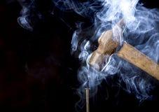 Det abstrakta fotoet av den rostiga hammaren för metall över spikar med rök på svart bakgrund arkivbilder