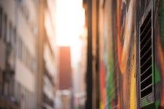 Det abstrakta stilfotografiet som ser ner en grafitti, fodrade grändwa royaltyfri bild