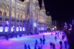 Det abstrakta suddiga folket åker skridskor på isen i nattstaden royaltyfri foto