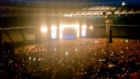 Det abstrakta suddiga fotoet av den stora folkmassan på vaggar konsert på stadion på natten Perfekt bakgrund för att illustrera p arkivbild