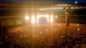 Det abstrakta suddiga fotoet av den stora folkmassan p? vaggar konsert p? stadion p? natten Perfekt bakgrund f?r att illustrera p arkivfoton