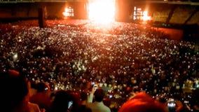 Det abstrakta suddiga fotoet av den stora folkmassan p? vaggar konsert p? stadion p? natten Perfekt bakgrund f?r att illustrera p arkivbild
