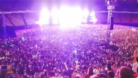 Det abstrakta suddiga fotoet av den stora folkmassan p? vaggar konsert p? stadion p? natten Perfekt bakgrund f?r att illustrera p arkivbilder