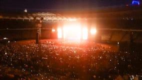 Det abstrakta suddiga fotoet av den stora folkmassan p? vaggar konsert p? stadion p? natten Perfekt bakgrund f?r att illustrera p royaltyfri bild