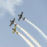 Det Aerobatic flygplanet lotsar utbildning i himlen av den Bucharest staden, Rumänien Kulört flygplan med spårrök Arkivbilder