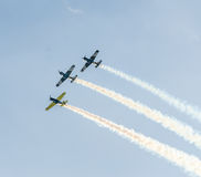 Det Aerobatic flygplanet lotsar utbildning i himlen av den Bucharest staden, Rumänien Kulört flygplan med spårrök Royaltyfri Bild