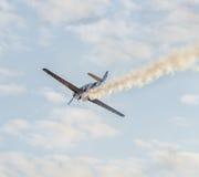 Det Aerobatic flygplanet lotsar utbildning i himlen av den Bucharest staden, Rumänien Kulört flygplan med spårrök Arkivfoton