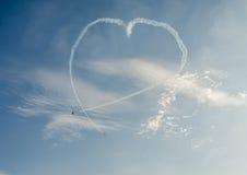 Det Aerobatic flygplanet lotsar utbildning i himlen av den Bucharest staden, Rumänien Kulört flygplan med spårrök Royaltyfri Foto