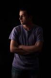 Det allvarliga anseendet för ung man med armar korsade på svart bakgrund Arkivbild