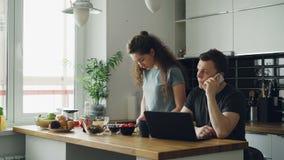 Det allvarliga caucasian paret i kök, kvinna är bitande sallad, henne står tyst, mannen sitter på tabellen som arbetar på arkivfilmer