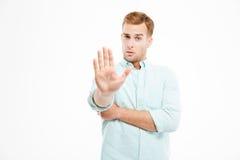 Det allvarliga unga affärsmananseendet och visningstoppet gör en gest Fotografering för Bildbyråer