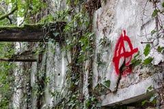 'Det anarki'symbolet graffitied i ett förstört fotografering för bildbyråer