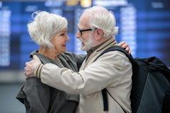 Det angenäma åldriga paret omfamnar i terminal fotografering för bildbyråer