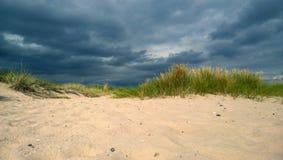 Det annalkande stormmolnet på stranden med dyn och ren vit sand arkivbilder