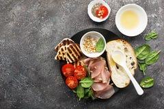 Det aptitretande mellanmålet med den stekte osthaloumien, oliv, bruschettaen, tomater, oliv, sörjer muttrar, olivolja, honung och arkivbild