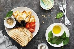 Det aptitretande mellanmålet med den stekte osthaloumien, oliv, bruschettaen, tomater, oliv, sörjer muttrar, olivolja, honung och fotografering för bildbyråer