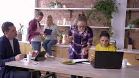 Det arbetande laget av lyckade unga businesspeople är äta och arbeta med minnestavlor och bärbara datorer i kök under framställni lager videofilmer
