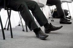 Det arbetslösa folket väntar deras vänd för en intervju som sitter på kontorsstolar i hallet Arbetslöshet- och jobbsökande arkivbilder