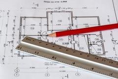 Det arkitektoniska planet av huset skrivs ut på ett vitt ark av papper En röd blyertspenna och en linjal på den arkivfoto
